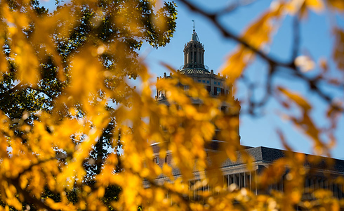 Flowering crabapple trees frame the George Eastman statue on the University of Rochester&#